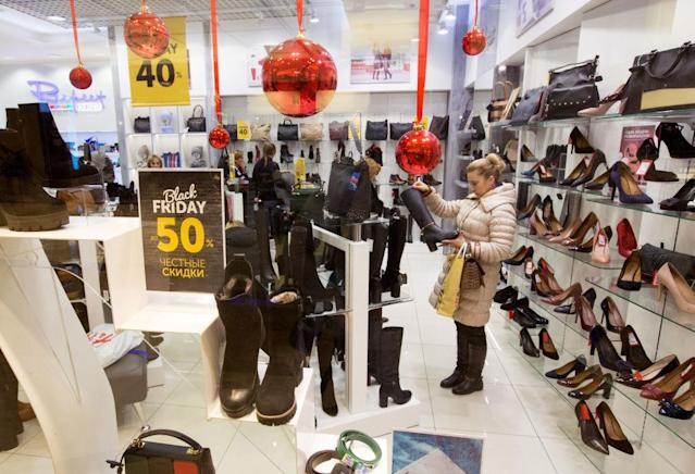 Customers browse discounted footwear inside a shoe store during Black Friday.