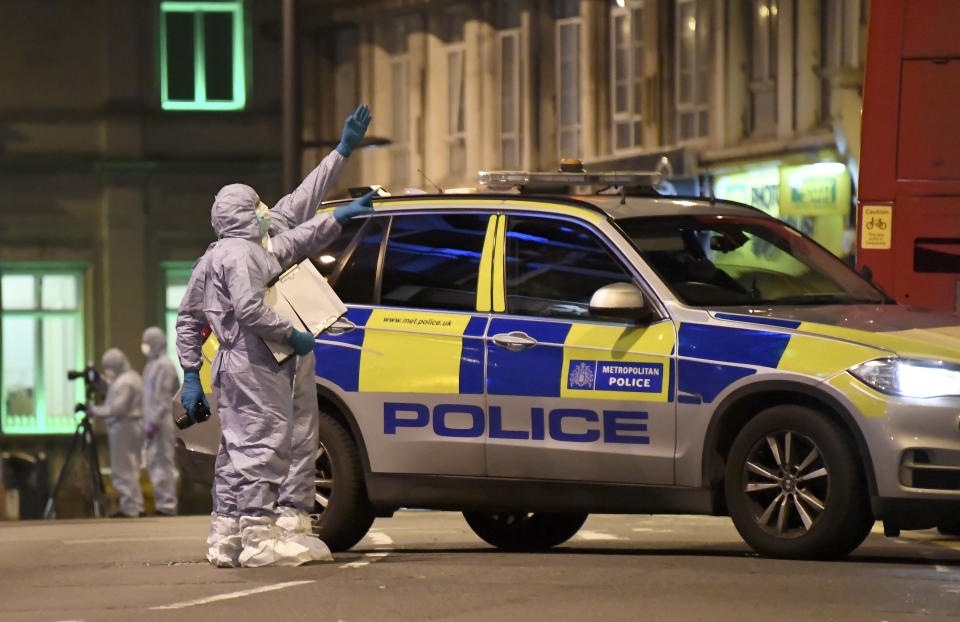 Police forensic officers work near the scene after a stabbing incident in Streatham London, England, Sunday, Feb. 2, 2020. London police officers shot and killed a suspect after at least two people were stabbed Sunday in what authorities are investigating as a terror attack. (AP Photo/Alberto Pezzali)