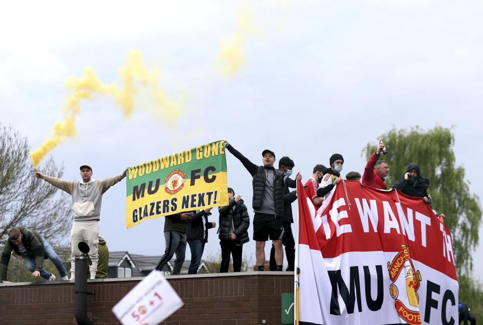 Fans holds up banners as they protest against the Glazer family, owners of Manchester United, before their Premier League match against Liverpool at Old Trafford, Manchester, England, Sunday, May 2, 2021. (Barrington Coombs/PA via AP)