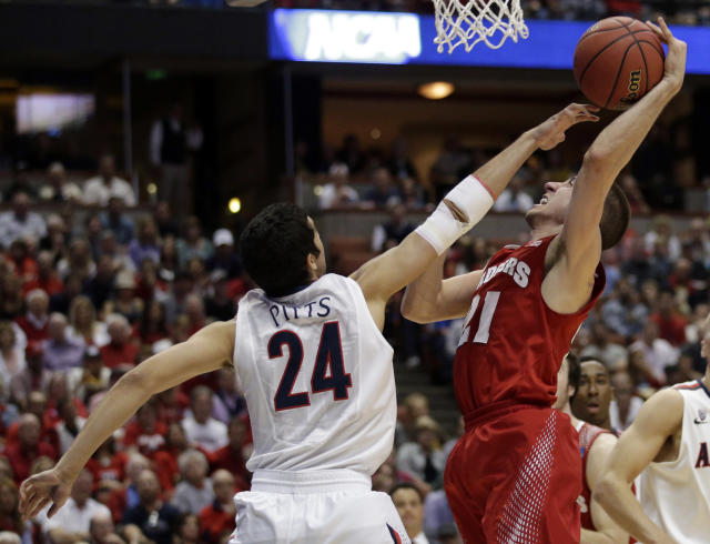 Wisconsin 's Josh Gasser (21) tries to shoot past Arizona's Elliott Pitts (24) during the first half in a regional final NCAA college basketball tournament game, Saturday, March 29, 2014, in Anaheim, Calif. (AP Photo/Jae C. Hong)