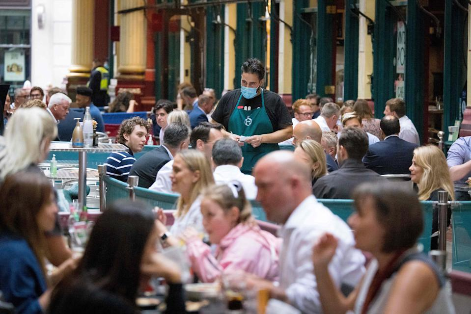 A waiter wearing a face mask serves customers at a restaurant in Leadenhall Market in the City of London on July 27, 2021. - Prime Minister Boris Johnson called for caution Tuesday after Britain registered nearly a week of lower coronavirus case numbers, a decline that has surprised officials and experts. (Photo by Tolga Akmen / AFP) (Photo by TOLGA AKMEN/AFP via Getty Images)