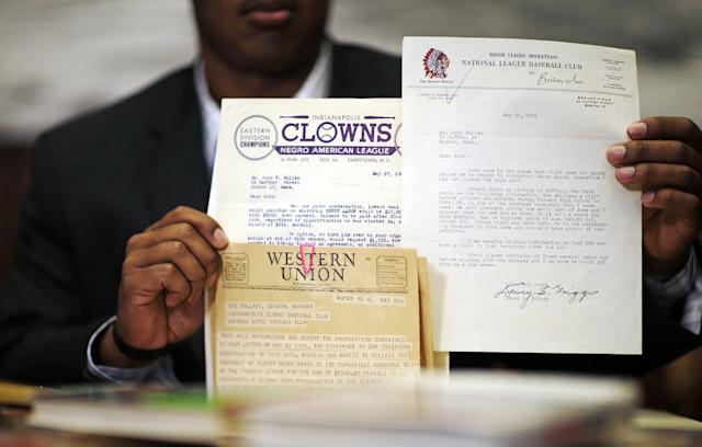 Emory University student Kyle Arbuckle, holds up some of the school's collection of Hank Aaron materials, Monday, April 7, 2014, in Atlanta. Arbuckle, along with classmates Warren Kember and Brett Lake teamed up last year to dig through the collection, donated in 2013 by a former scout for the Atlanta Braves, to create an exhibit opening on April 24 at the university's Robert W. Woodruff Library. (AP Photo/David Goldman)