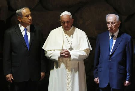 Pope Francis (C) stands in between Israeli Prime Minister Benjamin Netanyahu (L) and Israeli President Shimon Peres during a ceremony in the Hall of Remembrance at the Yad Vashem Holocaust memorial in Jerusalem May 26, 2014. REUTERS/Baz Ratner