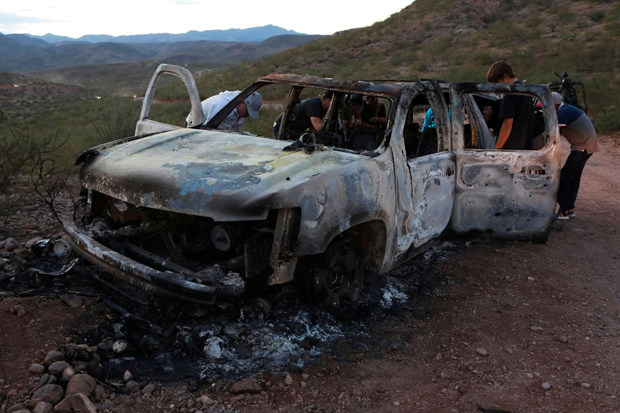 Members of the Lebaron family examine the burned car where some of the nine murdered members of the family were killed and burned in the Sonora mountains. (Photo: STR via Getty Images)
