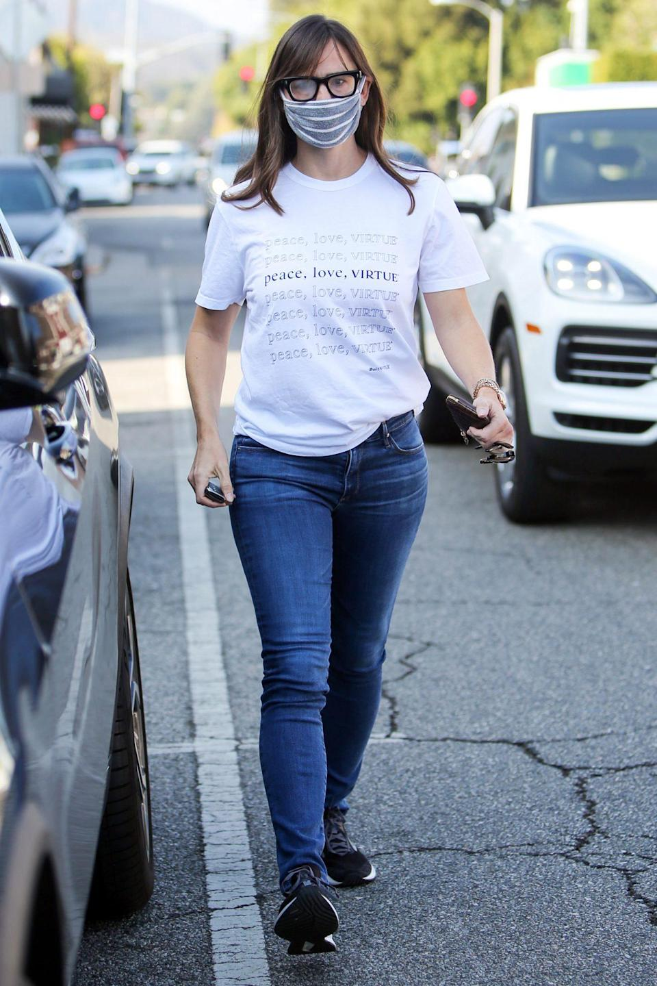 "<p>Jennifer Garner spreads good vibes in L.A. on Thursday while wearing a shirt that says, ""peace, love, VIRTUE."" </p>"