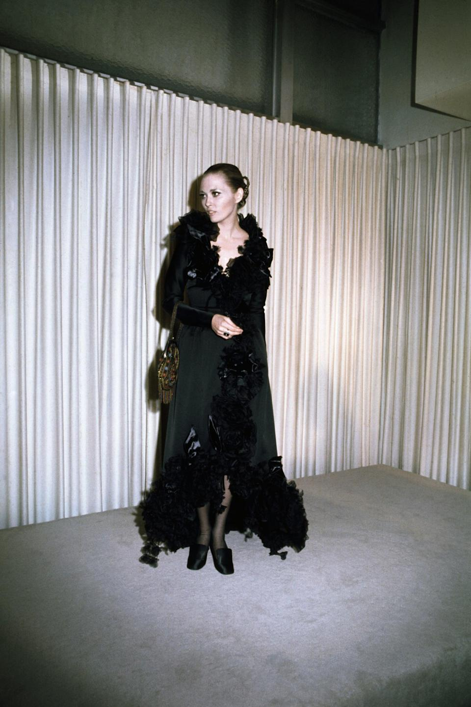 <p>Faye dominated this feathered Theadora Van Runkle gown. </p>