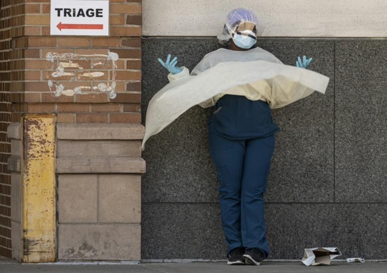 A medical worker takes a break outside a special COVID-19 area at Maimonides Medical Center in New York City (AFP Photo/Johannes EISELE)