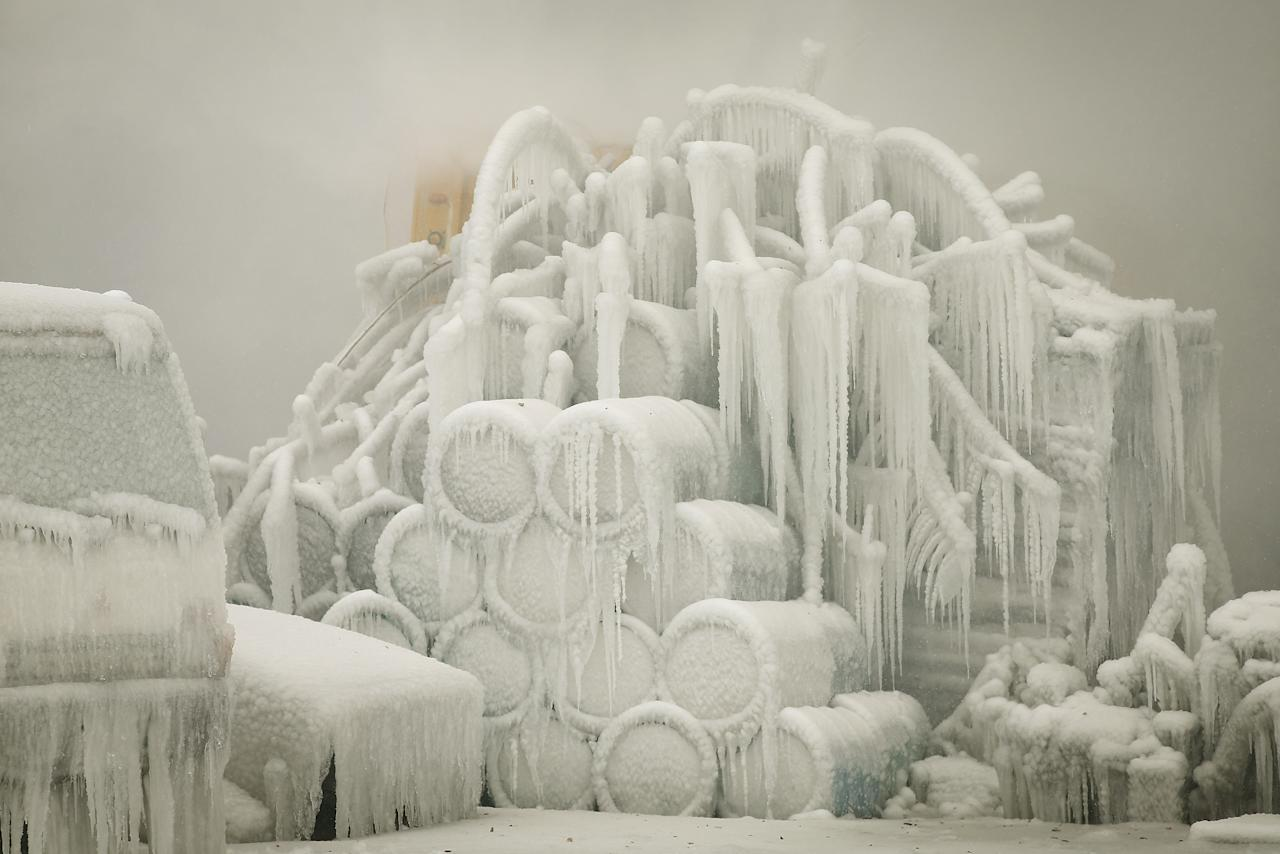 A truck and chemical drums are covered with ice as firefighters help to extinguish a massive blaze at a vacant warehouse on January 23, 2013 in Chicago, Illinois. More than 200 firefighters battled a five-alarm fire as temperatures were in the single digits. (Photo by Scott Olson/Getty Images)