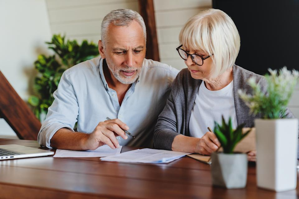 Mature couple with financial documents in home interior. Source: Getty Images
