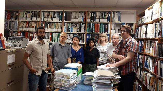 Staff at the Injured Workers Community Legal Clinic pose for a photo at their office. Each pile of documents relates to only one case, which staff says shows how complicated the law is around workers compensation.