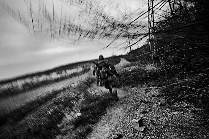 <p>A Ukrainian soldier runs for cover amid sniper fire from Russian-backed rebels on the frontline near Novotroitsk, in Donbass Oblast in Ukraine, April 2017. (Photo: Manu Brabo/MeMo) </p>