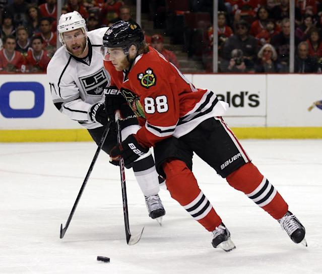 Chicago Blackhawks' Patrick Kane (88), right, controls the puck against Los Angeles Kings' Jeff Carter (77) during the first period in Game 1 of the Western Conference finals in the NHL hockey Stanley Cup playoffs in Chicago on Sunday, May 18, 2014. (AP Photo/Nam Y. Huh)
