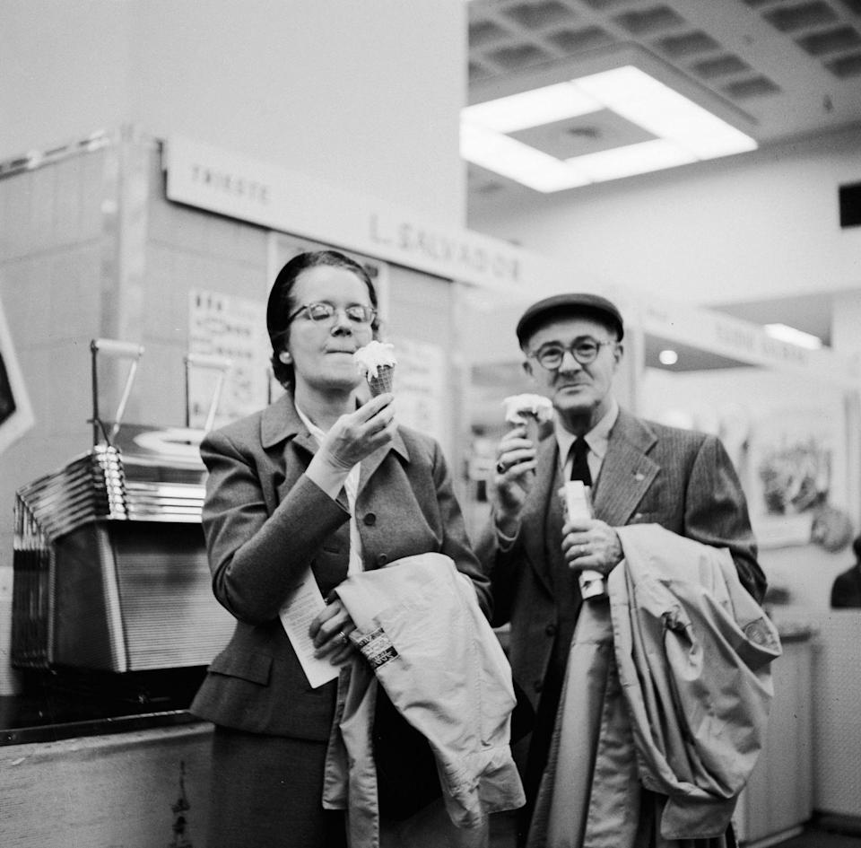 <p>An older couple stands near the ice cream counter as they enjoy their cones together.</p>