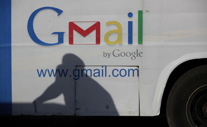 In this photo taken, Monday, Sept. 17, 2012. An unidentified man's shadow reflects on a commercial bus with an advertisement for Google Mail, in Lagos, Nigeria. With all its cutting-edge technology, Google Inc. has turned back to the text message in its efforts to break into Nigeria's booming economy. The search engine has started a service in Nigeria, as well as Ghana and Kenya, allowing mobile phone users to access emails through text messaging. That comes as the company's office in Lagos has begun working with small business owners in this nation of more than 160 million people. (AP Photo/Sunday Alamba)