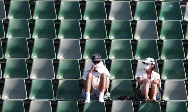 Tennis fans protect themselves from the sun during a first round match at the Australian Open tennis championship in Melbourne, Australia, Tuesday, Jan. 14, 2014.(AP Photo/Aaron Favila)