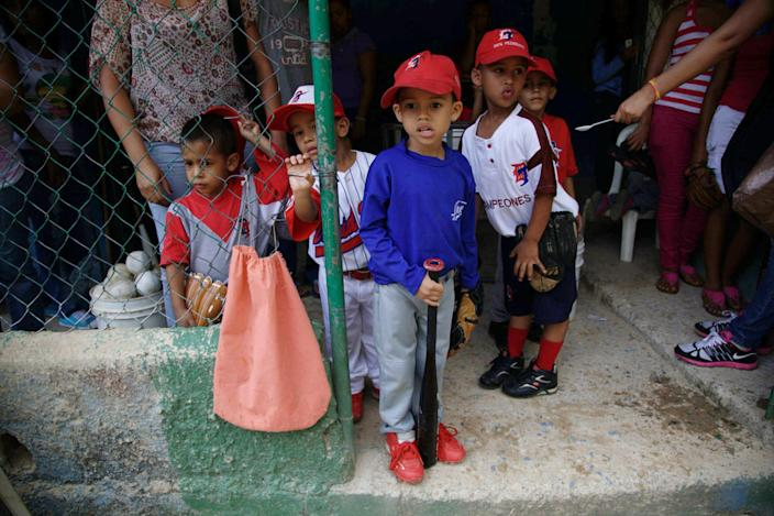 In this Oct. 25, 2012 photo, children wait for the start of training at a baseball school in Maracay, Venezuela. Many of the boys are inspired by the example of Detroit Tigers slugger Miguel Cabrera, who learned the game on this very field. Their baseball school in the poor neighborhood where Cabrera grew up is one of many across Venezuela, a web for training young ballplayers that has made the country a powerhouse in the U.S. major leagues. (AP Photo/Ariana Cubillos)