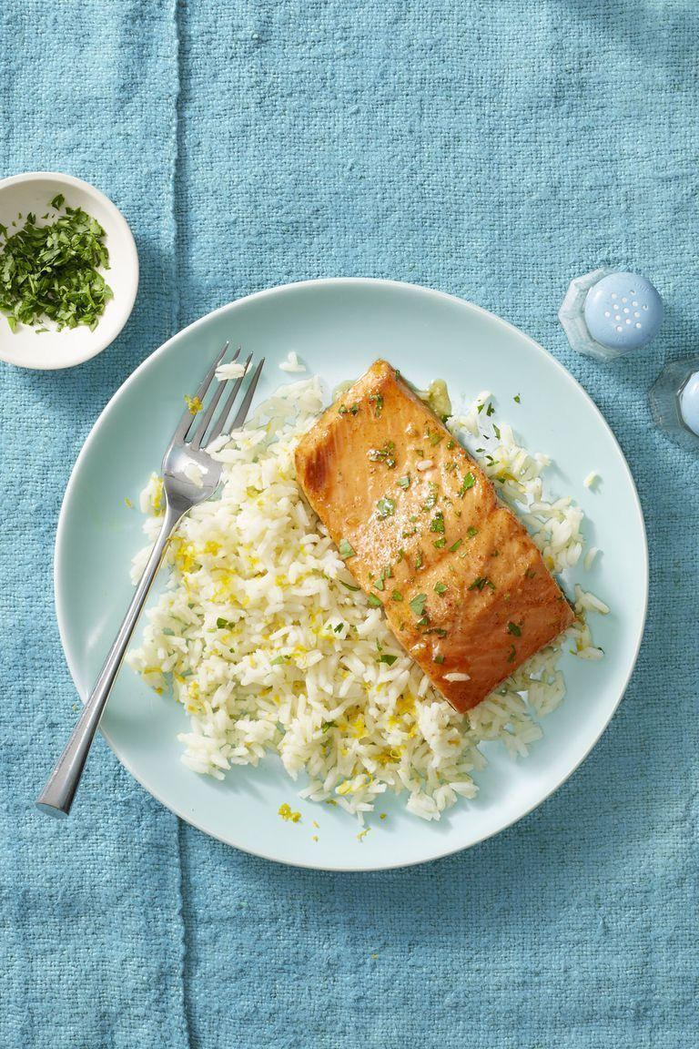 """<p>When baking salmon, sometimes straightforward <em>is </em>best. Here, we add fillets to a parchment-lined baking sheet, top with a drizzle of lemon-butter and sprinkle of parsley, and bake. </p><p><em><a href=""""https://www.womansday.com/food-recipes/food-drinks/a24132425/garlic-butter-salmon-and-citrus-rice-recipe/"""" rel=""""nofollow noopener"""" target=""""_blank"""" data-ylk=""""slk:Get the recipe for Garlic Butter Salmon and Citrus Rice"""" class=""""link rapid-noclick-resp"""">Get the recipe for Garlic Butter Salmon and Citrus Rice</a></em></p>"""