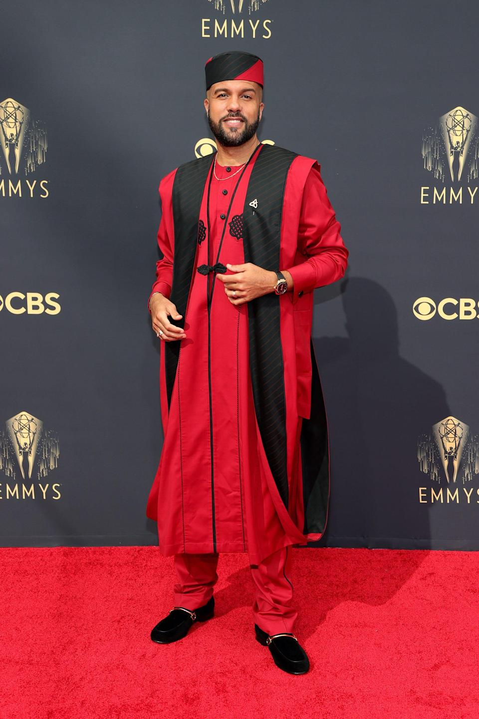 O-T Fagbenl wears a red and black outfit on the Emmys red carpet.