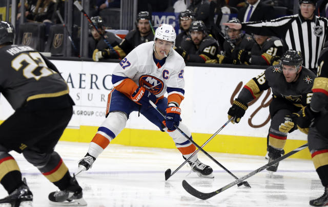 New York Islanders forward Anders Lee (27) looks to pass the puck as Vegas Golden Knights center Paul Stastny (26) defends during the third period of an NHL hockey game Saturday, Feb. 15, 2020, in Las Vegas. The Golden Knights won 1-0. (AP Photo/Isaac Brekken)