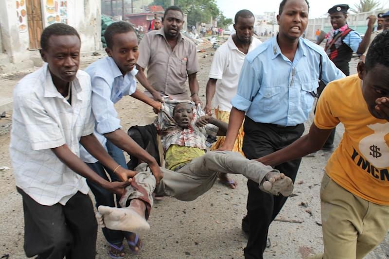 Somalis carry a man who was wounded by a suicide bomber who detonated his explosives near a moving convoy of African union troops, in Mogadishu, Somalia, Friday, July,12 , 2013. Police have said that at least two people were killed and seven were injured in the blast. (AP Photo/Farah Abdi Warsameh)