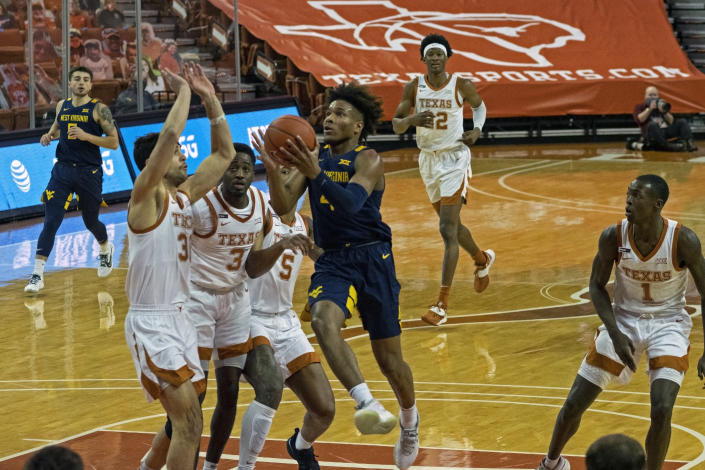 West Virginia guard Miles McBride (4) drives the ball against Texas forward Brock Cunningham (30) during the first half of an NCAA college basketball game, Saturday, Feb. 20, 2021, in Austin, Texas. (AP Photo/Michael Thomas)