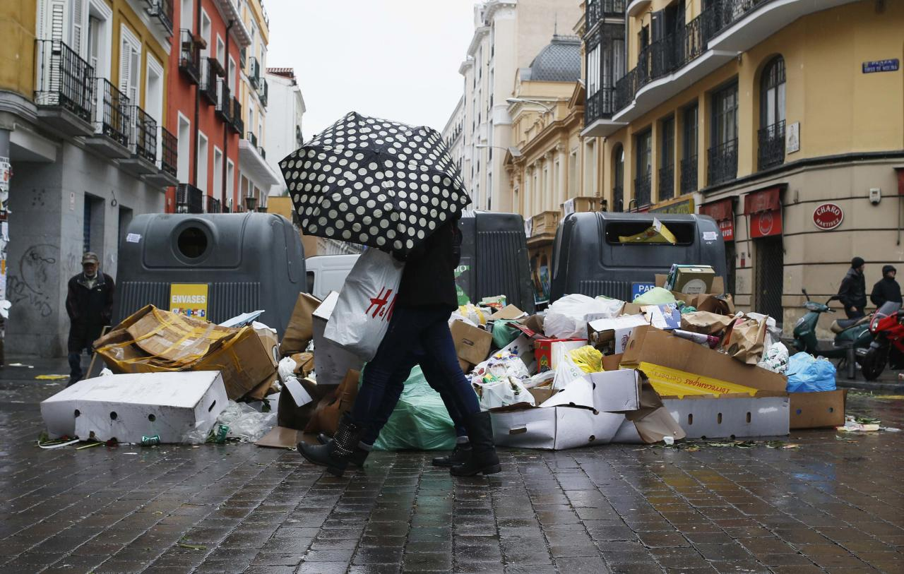 A pedestrian walks next to garbage strewn on the pavement during a strike by street cleaners in Madrid November 17, 2013. A 12-day strike by street sweepers that left Madrid littered with garbage was set to end on Sunday after private maintenance companies cancelled plans to lay off a fifth of the Spanish capital's street cleaners. The cleaners walked off the job on November 5 after three companies with maintenance contracts with city hall sought to freeze salaries and lay off 1,134 out of 6,000 workers. REUTERS/Javier Barbancho (SPAIN - Tags: BUSINESS EMPLOYMENT CIVIL UNREST ENVIRONMENT POLITICS)