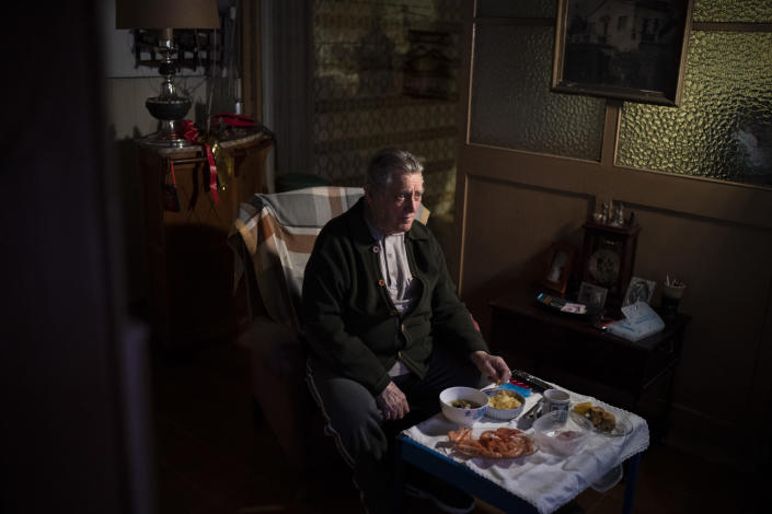 """Álvaro Puig Moreno watches television while eating a his Christmas Eve dinner at his home in Barcelona, Spain, Dec. 24, 2020. """"The solitude gets to me these days, I often feel depressed,"""" Puig said. """"These holidays, instead of making me happy, make me sad. I hate them. Most of family has died, I am one of the last ones left. I will spend Christmas at home alone because I don't have anyone to spend them with."""" The image was part of a series by Associated Press photographer Emilio Morenatti that won the 2021 Pulitzer Prize for feature photography. (AP Photo/Emilio Morenatti)"""