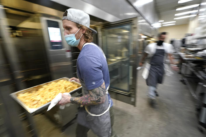 "Kevin Benner, a chef at The Lakehouse, a restaurant located in Bellevue, Wash., carries a tray of potato cakes as he works in the kitchen at Lumen Field, Thursday, Feb. 18, 2021, in Seattle. Benner was one of the chefs taking part in the inaugural night of the ""Field To Table"" event at stadium, which is home to the Seattle Seahawks NFL football team. The event will feature several weeks of dates that offer four-course meals cooked by local chefs and served at tables socially distanced as a precaution against the COVID-19 pandemic. (AP Photo/Ted S. Warren)"