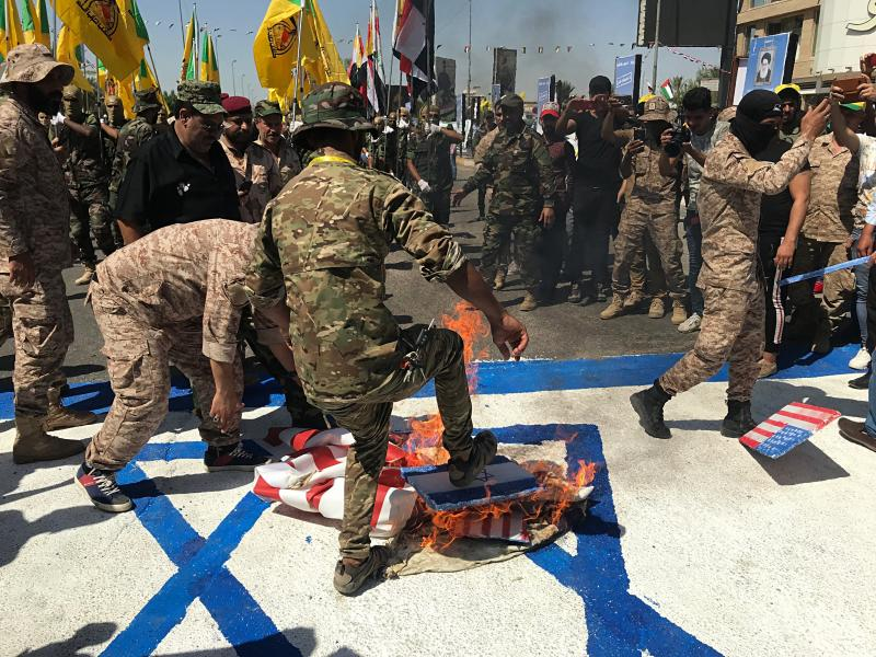 """Iraqi Popular Mobilization Forces burn representations of U.S. and Israeli flags during """"al-Quds"""" Day, Arabic for Jerusalem, in Baghdad, Iraq, Friday, May 31, 2019. Jerusalem Day began after the 1979 Islamic Revolution in Iran, when the Ayatollah Khomeini declared the last Friday of the Muslim holy month of Ramadan a day to demonstrate the importance of Jerusalem to Muslims. (AP Photo/Ali Abdul Hassan)"""
