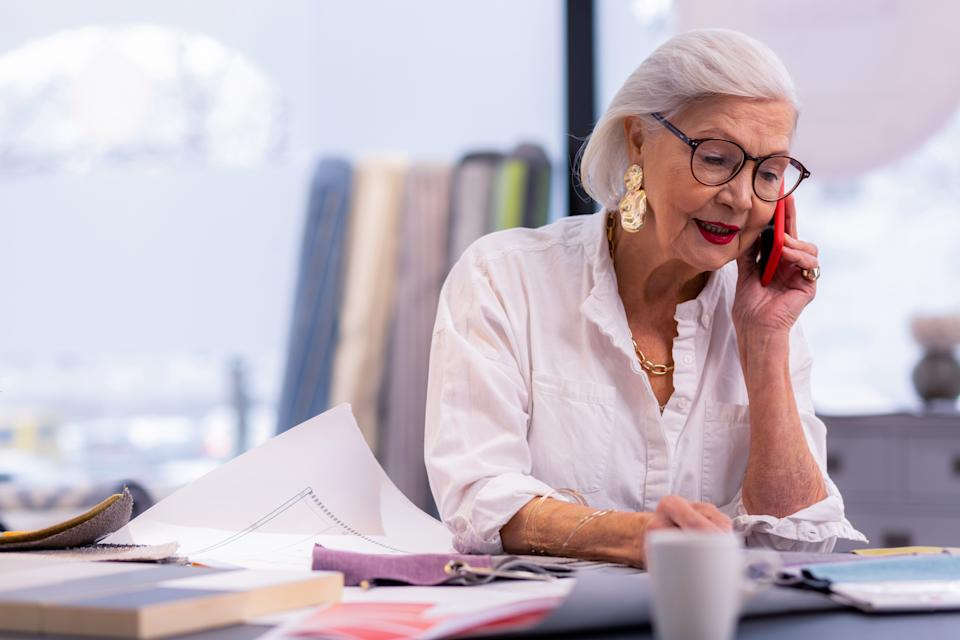 Telephone conversation. Enchanting well-groomed aging boss in white stylish shirt and trendy accessories busily speaking on the phone in office.
