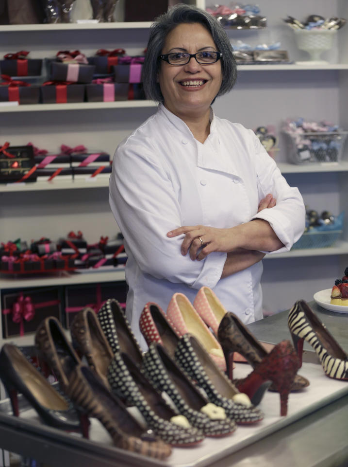 In this Feb. 7, 2013 photo, master chocolatier Andrea Pedraza shows off her chocolate shoes and other treats at her shop in the Oak Cliff section of Dallas. Florists and chocolate makers are working around the clock for the busy season - Valentine's Day. Pedraza's most well known creations are chocolate pumps done in the style of Christian Louboutin shoes. (AP Photo/LM Otero)