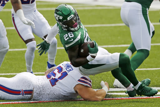 New York Jets running back Le'Veon Bell (26) is brought down by Buffalo Bills' Justin Zimmer (61) during the first half of an NFL football game in Orchard Park, N.Y., Sunday, Sept. 13, 2020. (AP Photo/John Munson)