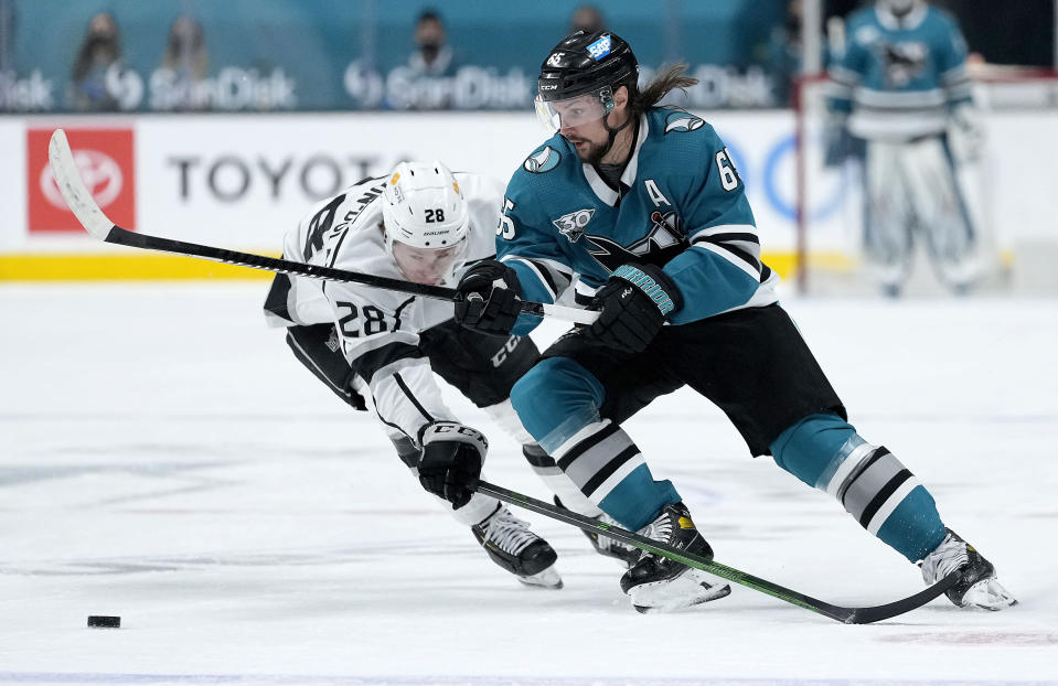 San Jose Sharks defenseman Erik Karlsson (65) moves the puck past Los Angeles Kings center Jaret Anderson-Dolan (28) during the third period of an NHL hockey game Saturday, April 10, 2021, in San Jose, Calif. The Kings won 4-2. (AP Photo/Tony Avelar)