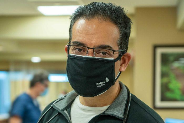 A man in a black face mask standing in a hospital ward