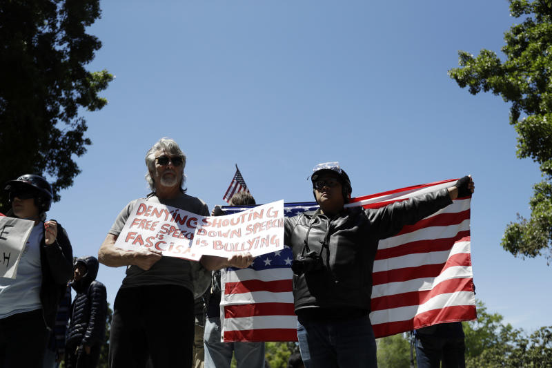 Demonstrators hold flags and signs Thursday, April 27, 2017, in Berkeley, Calif. Demonstrators gathered near the University of California, Berkeley campus amid a strong police presence and rallied to show support for free speech and condemn the views of Ann Coulter and her supporters. (AP Photo/Marcio Jose Sanchez)