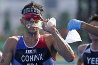 Dorian Coninx of France takes water as a volunteer holds out a bag of ice, during the run portion of the men's individual triathlon at the 2020 Summer Olympics, Monday, July 26, 2021, in Tokyo, Japan. (AP Photo/Jae C. Hong)