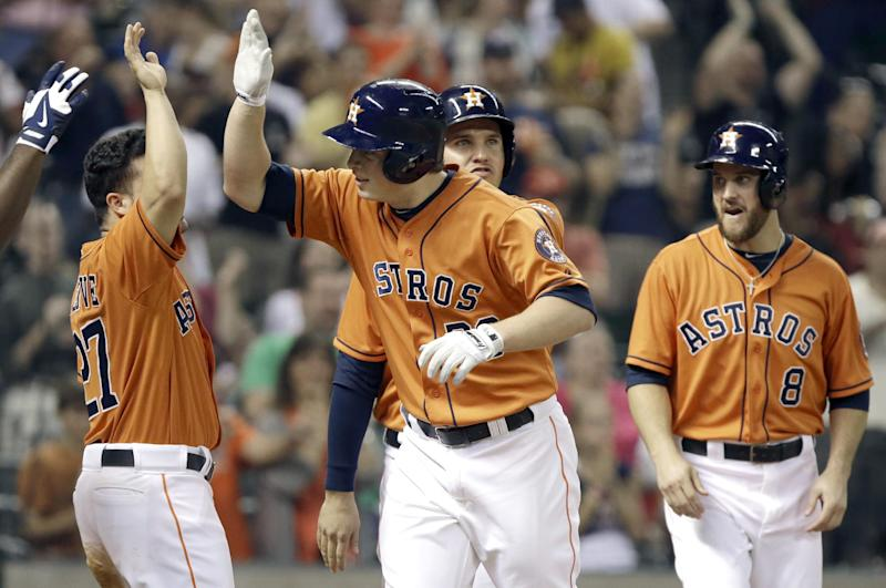 Houston Astros' Matt Dominguez, second from left, is welcomed at home plate by teammates Jose Altuve, left, Brandon Laird, center, and Trevor Crowe (8) on a grand slam against the Los Angeles Angels in the fifth inning of a baseball game Friday, Sept. 13, 2013, in Houston. (AP Photo/Pat Sullivan)