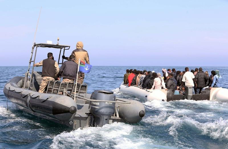 Libyan coast guards escort a boatload of migrants, who had hoped to set off to Europe with the help of people smugglers from the coastal town of Garabulli, on June 6, 2015 (AFP Photo/Mahmud Turkia)
