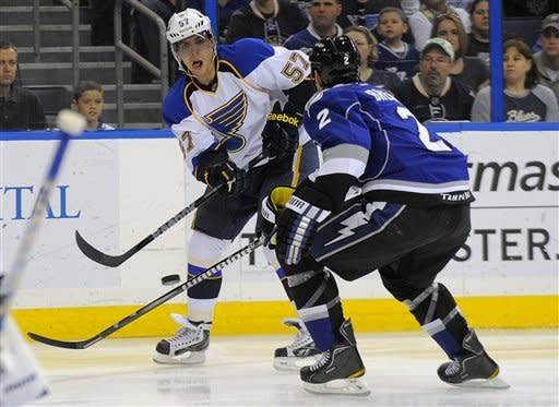 St. Louis Blues left wing David Perron, left, takes a shot against Tampa Bay Lightning defenseman Eric Brewer during the first period of an NHL hockey game, Saturday, March 17, 2012, in Tampa, Fla. (AP Photo/Brian Blanco)