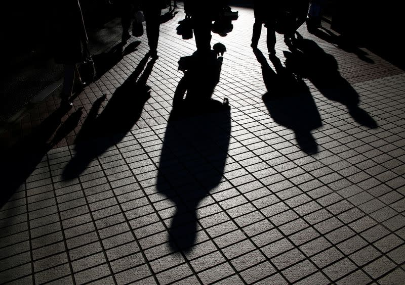 Pedestrians cast shadows as they make their way at a financial district in Tokyo