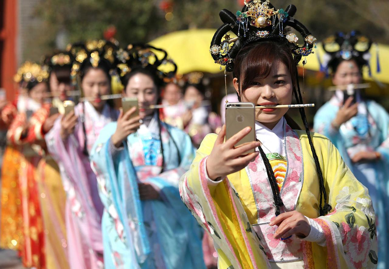 <p>Tour guides wearing traditional Chinese dress practice smiling by biting chopsticks at Qingming Grand-River Park in Kaifeng, central China's Henan Province on March 2, 2017, aiming to provide better service for visitors. (IPA Asia via ZUMA Wire) </p>
