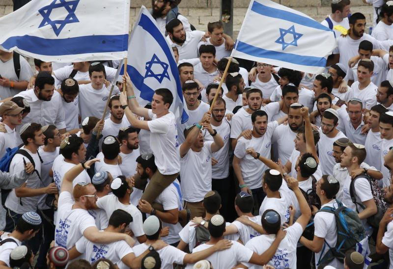 FILE - In this Sunday, May 13, 2018, file photo, Israeli youths wave national flags outside the Old City's Damascus Gate, in Jerusalem. Israel's parliament has approved a controversial piece of legislation that defines the country as the nation-state of the Jewish people. Opponents and rights groups have criticized the legislation, warning that it will sideline minorities such as the country's Arabs. (AP Photo/Ariel Schalit)