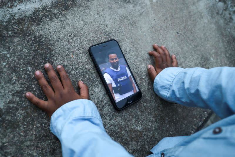 Son of Reuters cameraman Kumerra Gemechu displays his father's picture on a cell phone in a playground in Addis Ababa