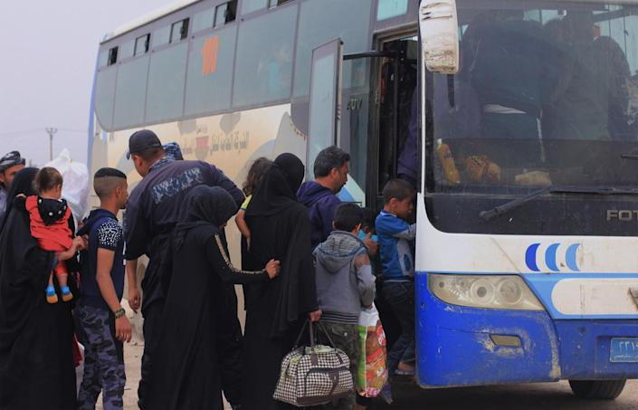Having fled their home only weeks before, residents of Mosul board a bus to return. (Photo: Ash Gallagher for Yahoo News)