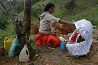 Saturnina Perez, aunt of late Yesmin Anayeli, holds the split lid of her niece's coffin before her burial at a hilltop, in La Palmilla