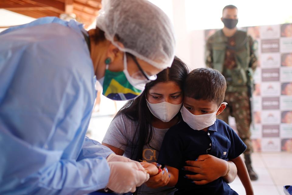 A member of the Brazilian Armed Forces medical team examines a child from the Guajajara indigenous ethnic group, amid the spread of the coronavirus disease (COVID-19), at a community school in the indigenous village of Morro Branco in the municipality of Grajau, state of Maranhao, Brazil October 4, 2020. REUTERS/Adriano Machado