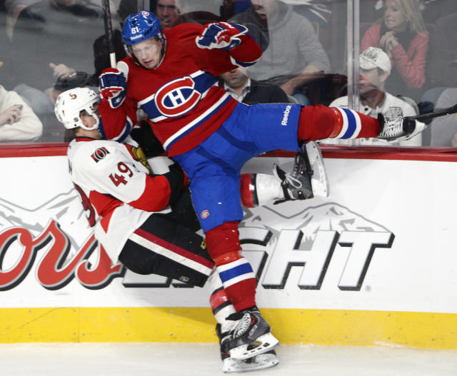 Ottawa Senators' Fredrik Claesson, of Sweden, is checked by Montreal Canadiens' Lars Eller, of Denmark, during the third period of an NHL preseason hockey game, Thursday, Sept. 26, 2013 in Montreal. (AP Photo/The Canadian Press, Ryan Remiorz)