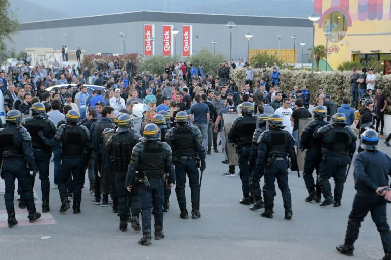 French anti-riot policemen stand guard the stadium exit as Bastia's supporters wait for the Lyon's players coach to leave after the French L1 football match Bastia vs Lyon on April 16, 2017