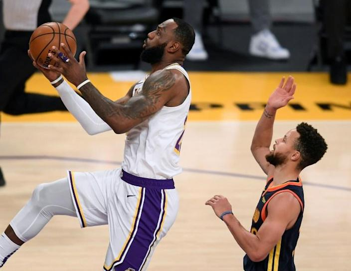 Los Angeles star LeBron James scores on a layup past Golden State's Stephen Curry in the Lakers' 117-91 NBA victory over the Warriors