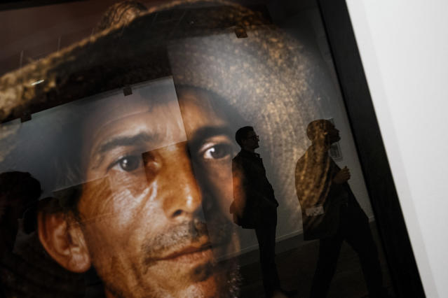 <p>Visitors are reflected in a framed picture by Andres Serrano at the ARCO International Contemporary Art Fair in Madrid, Feb. 22, 2017. (Photo: Daniel Ochoa de Olza/AP) </p>